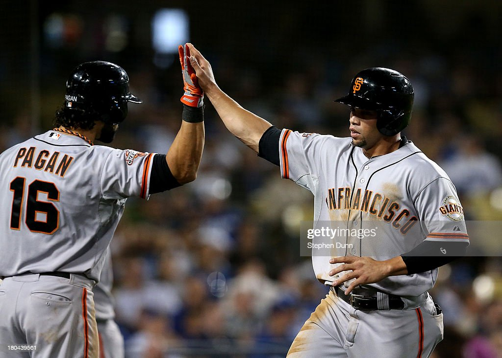 Pinch runner Juan Perez #2 of the San Francisco Giants is greeted by <a gi-track='captionPersonalityLinkClicked' href=/galleries/search?phrase=Angel+Pagan&family=editorial&specificpeople=666596 ng-click='$event.stopPropagation()'>Angel Pagan</a> #16 after Perez scored the tying run in the ninth inning against the Los Angeles Dodgers at Dodger Stadium on September 12, 2013 in Los Angeles, California.