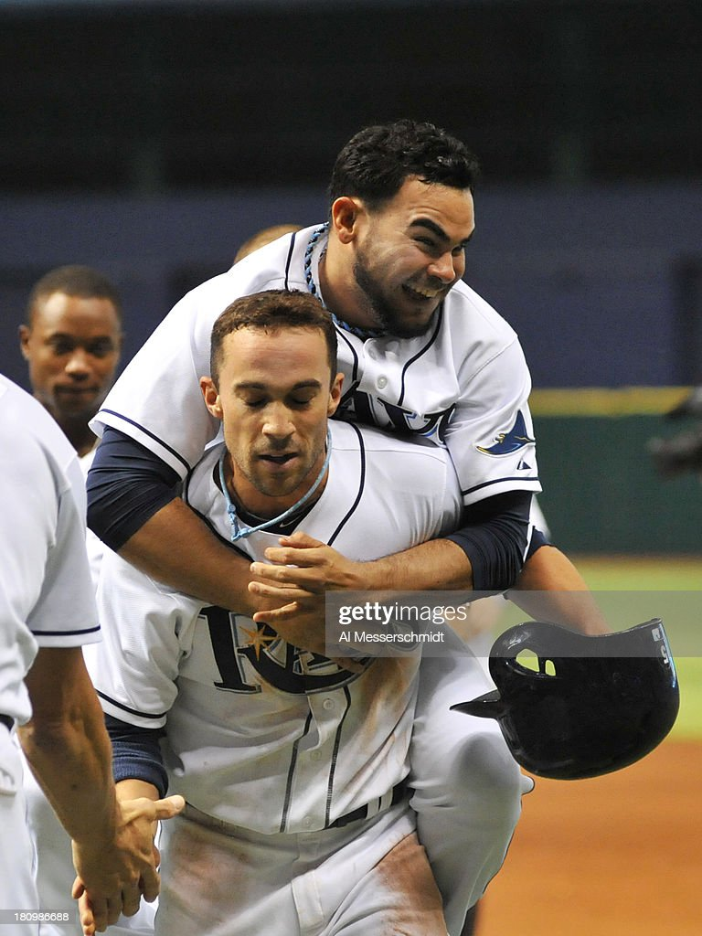 Pinch runner Sam Fuld #5 of the Tampa Bay Rays celebrates with relief pitcher Brandon Gomes #47 after scoring the winning run in the 12th inning against the Texas Rangers September 18, 2013 at Tropicana Field in St. Petersburg, Florida. The Rays won 4 - 3 and Gomes was the winning pitcher.