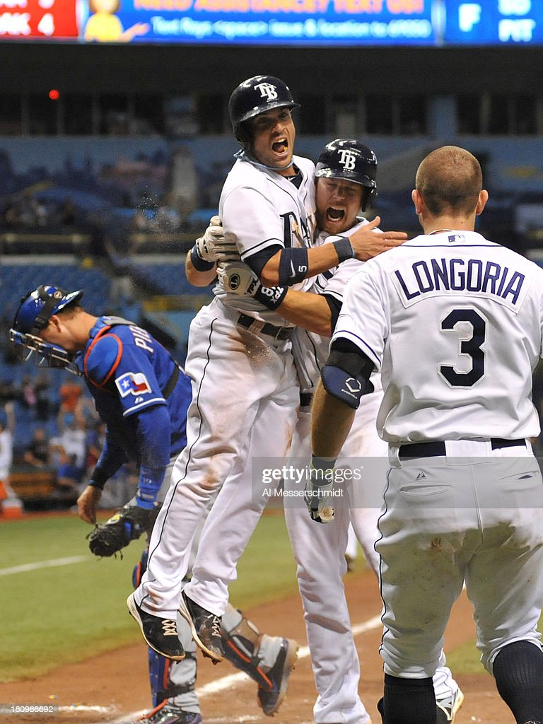 Pinch runner <a gi-track='captionPersonalityLinkClicked' href=/galleries/search?phrase=Sam+Fuld&family=editorial&specificpeople=4505687 ng-click='$event.stopPropagation()'>Sam Fuld</a> #5 of the Tampa Bay Rays celebrates with teammates after scoring the winning run in the 12th inning against the Texas Rangers September 18, 2013 at Tropicana Field in St. Petersburg, Florida. The Rays won 4 - 3.
