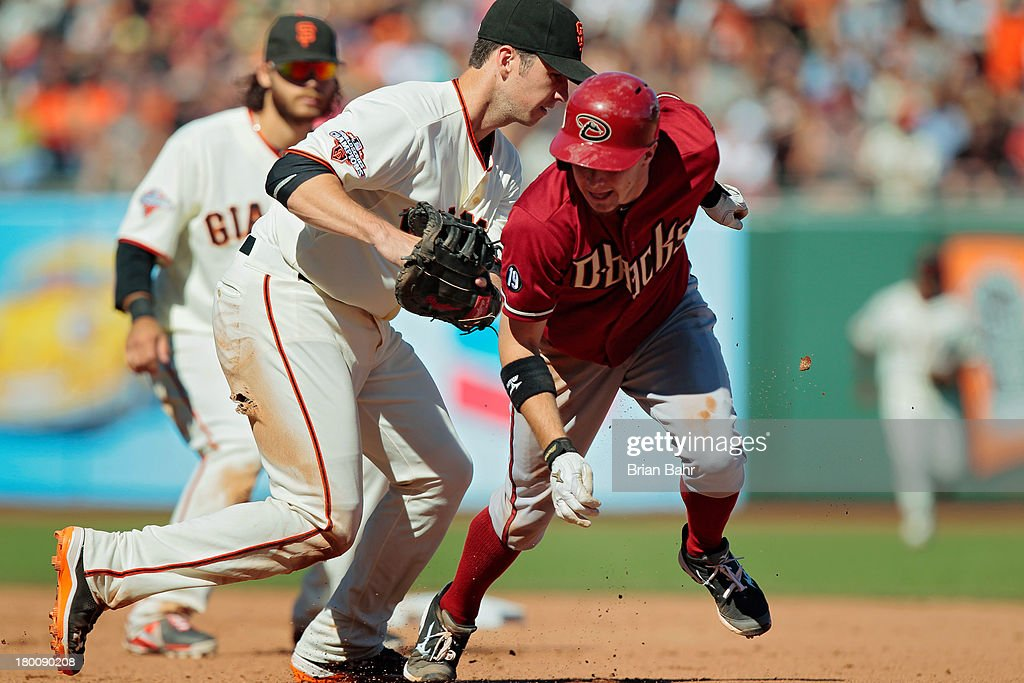 Pinch runner Tony Compana #19 of the Arizona Diamondbacks gets caught in a run-down between first and second base by first baseman <a gi-track='captionPersonalityLinkClicked' href=/galleries/search?phrase=Buster+Posey&family=editorial&specificpeople=4896435 ng-click='$event.stopPropagation()'>Buster Posey</a> #28 of the San Francisco Giants in the 10th inning at AT&T Park on September 8, 2013 in San Francisco, California. The Giants won 3-2 in 11 innnings.