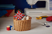 Pincushion like Union Jack in a wicker basket, sewing machine, sewing accessories