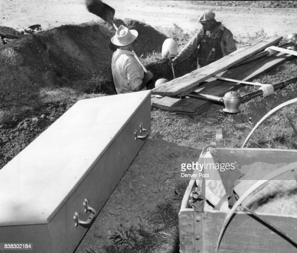 A pine box bearing the mutilated body of Irene Espinosa trunk murder victim rests on a mound of dirt as John Evans and George Malpiede prepare a...