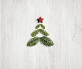 Photography of a christmas tree made of Pine branches on white painted wood planks.
