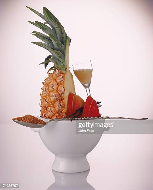 Pineapple, mango, spoon and juice glass in bowl on white background, close-up
