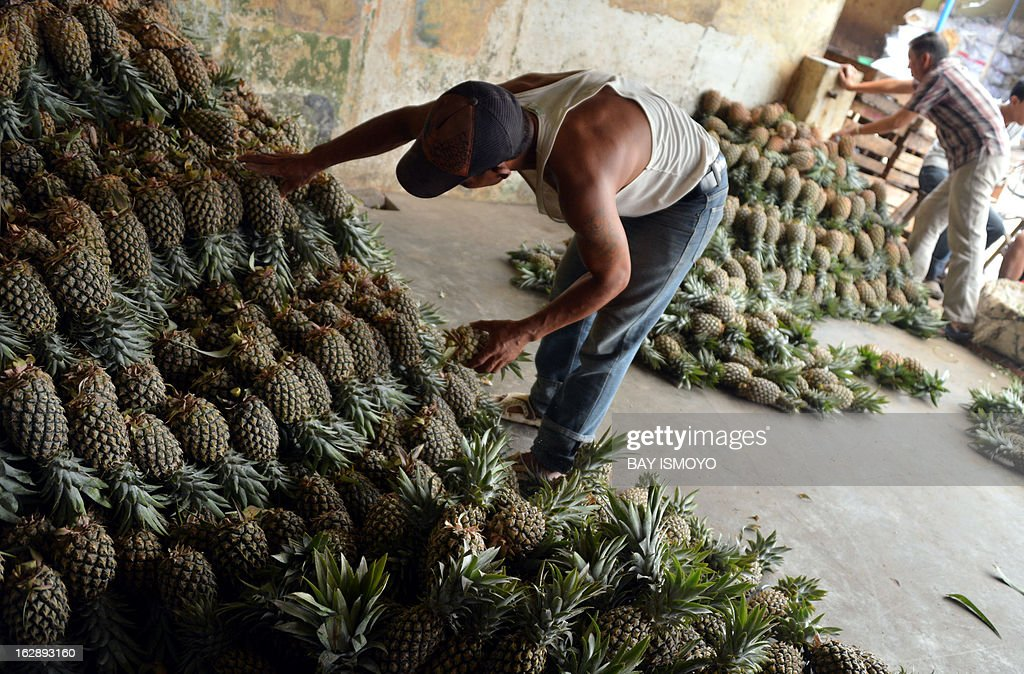 Pineapple vendors arrange fruits at Anyar market in Tangerang, Banten province, on March 1, 2013. Indonesian inflation in February hit a 20-month high after government measures to limit commodity imports pushed up consumer prices, an official said. AFP PHOTO / Bay ISMOYO