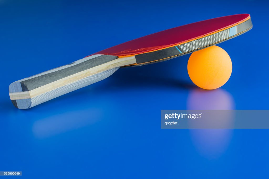 Ping-pong racket with a orange ball : Stock Photo