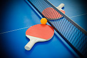 pingpong rackets and ball highlighted on a blue pingpong table