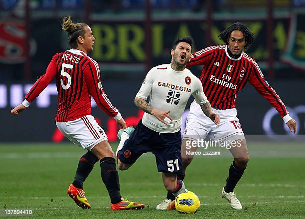 Pinilla of Cagliari Calcio competes for the ball with Philippe Mexes and Alessandro Nesta of AC Milan during the Serie A match between AC Milan and...