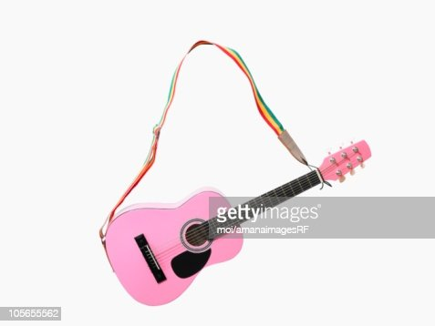 A Pink Acoustic Guitar With a Rainbow Colored Strap : Stock Photo