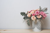 Bouquet of pink and beige roses in a decorative vase on a shelf in home interior, simple home decor
