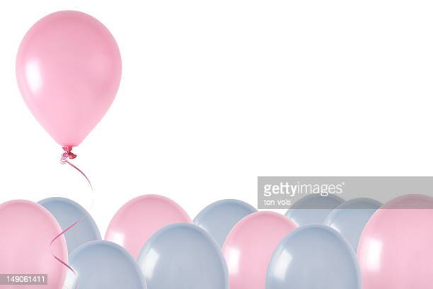 Pink and blue balloons, one rising