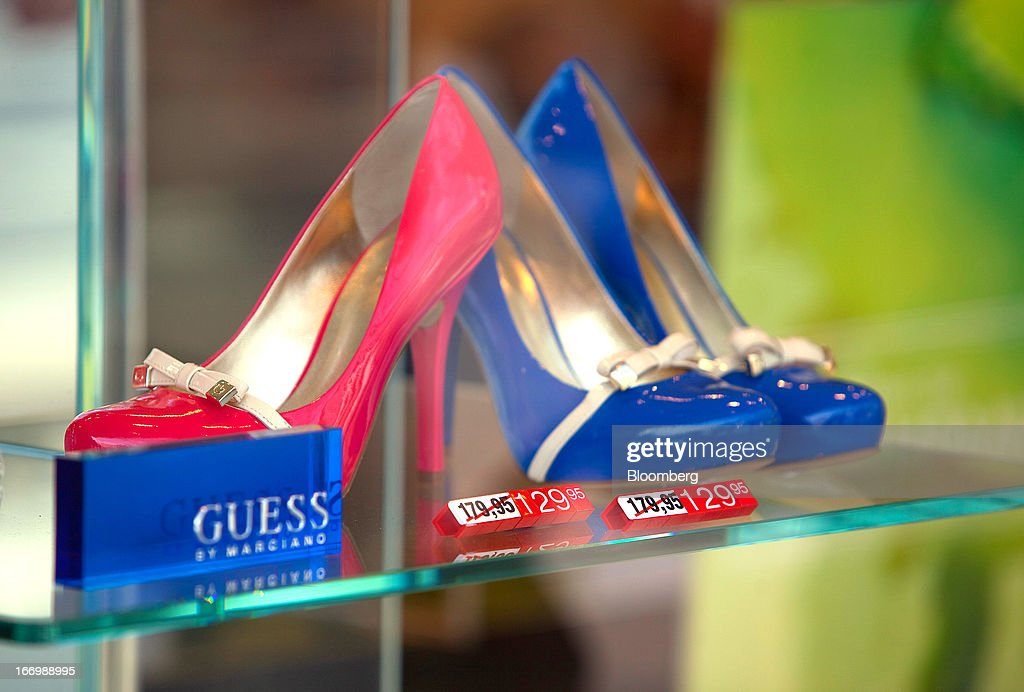 Pink and blue ladies shoes by Guess? Inc., are reduced in price in a window display of the Peek & Cloppenburg store in Berlin, Germany, on Thursday, April 18, 2013. Germany's economy is shrugging off a contraction at the end of last year and starting to grow due to revived exports and rising private consumption, the country's leading economic institutes said. Photographer: Krisztian Bocsi/Bloomberg via Getty Images