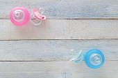 Pink and Blue pacifiers and baby bottles representing both girl and boy. Empty space for editor's text. Copy space.