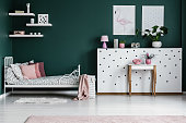 Pink pillow on patterned bed in green bedroom interior with posters on the wall