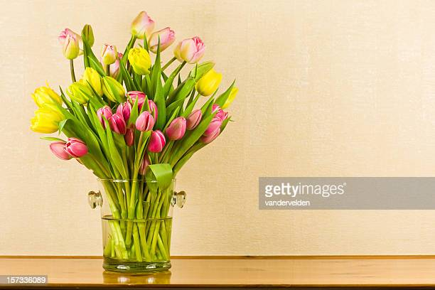 Pink and yellow tulips in a glass vase