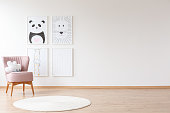 Pink armchair with pillow and white round carpet in baby's room with posters on wall with copy space