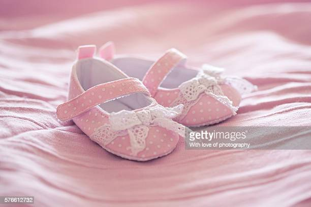 pink baby shoes on pink blanket. It's a girl!