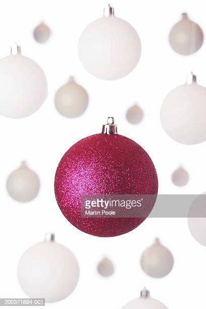 Pink bauble hanging in front of white ones, close up