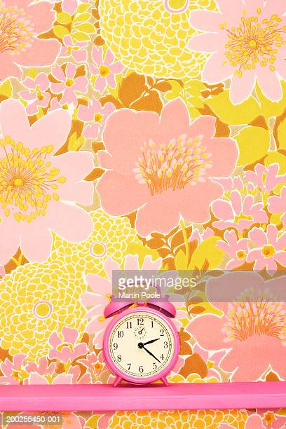 Pink bell alarm clock on shelf by floral wallpaper