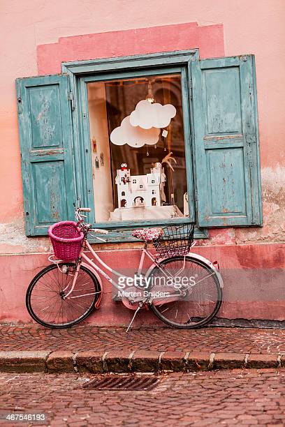 Pink bicycle against old wall with window
