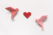 Pink Birds and Red Heart of origami on white background. Gift card for Valentine's Day. Concept sublime love.