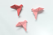 Pink Birds of different shades. Origami on light background. The concept of freedom, inspiration.