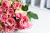 Bunch of pink roses on white wooden table