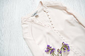Pink blouse with buttons and wildflowers. Fashionable concept