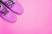 Pink boots on pink background. Copyspace, flat lay. Traveling boots, minimalist style. pink photofilter