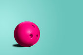 A toy bowling ball of pink color on a blue, turquoise pastel background. A minimalist concept, abstract. The concept of having fun, going out with friends.