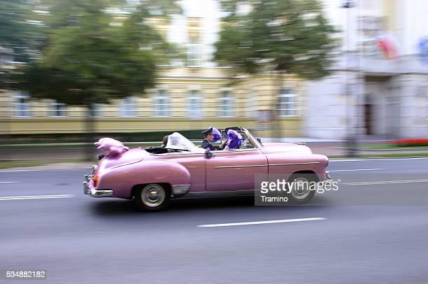 Pink Cadillac wedding car in motion