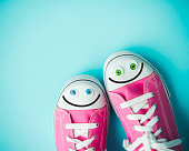 Pink canvas shoes with happy faces on blue background