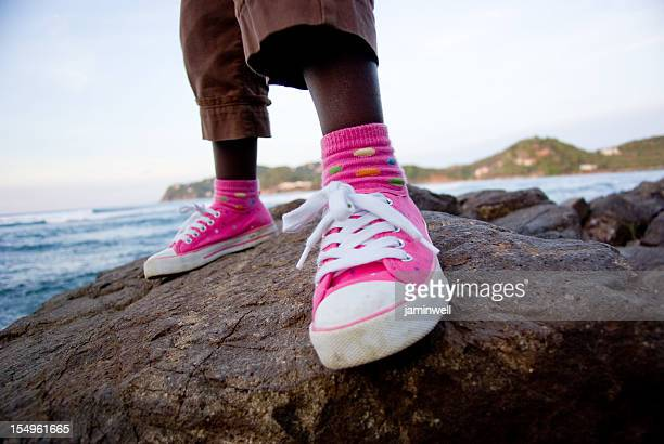 pink casual shoes chilling on rocks near beach