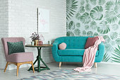 Green table with plant between pink chair and blue sofa in floral living room with wallpaper and poster