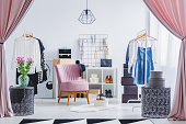 Pink chair in dressing room with flowers on designer table and clothes on hangers. Fashionable dressing room concept