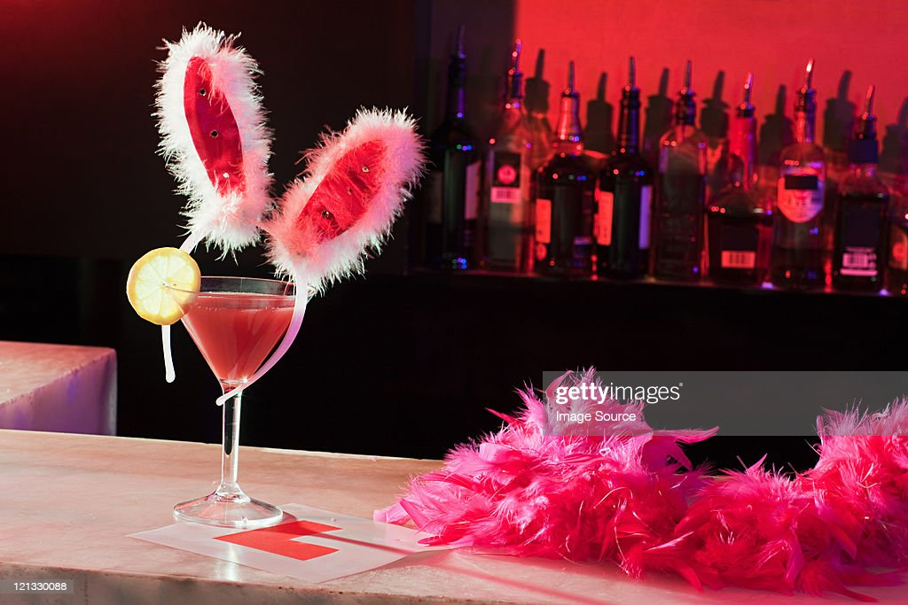 Pink cocktail, bunny ears and L plate on bar