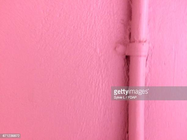 Pink colored painted wall with pipe