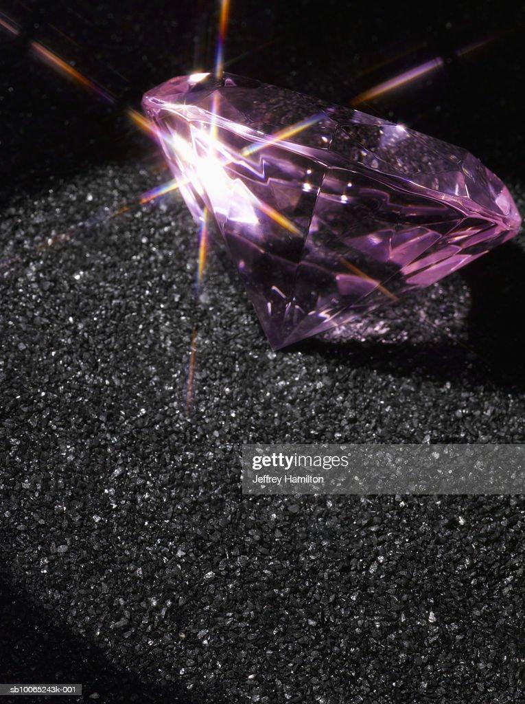 Pink diamond on black sand, close-up : Stock Photo