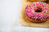 Pink donuts on paper on a wooden background. Delicious dessert.