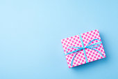Pink dotted gift box on blue background. Close up