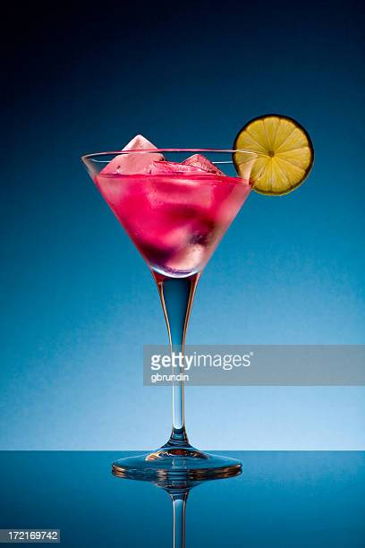 Pink drink in a cocktail glass with a lemon wedged on