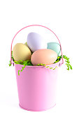 A Pink Easter Basket Filled with Decorated Eggs Isolated on a White Background