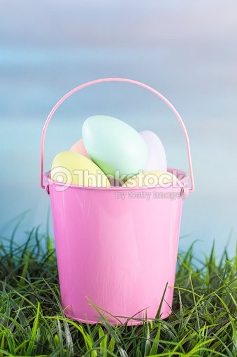 A Pink Easter Basket Filled with Diecorated Eggs on a Clear Blue Sky Spring Day : Stock Photo