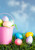 A Pink Easter Basket Filled with Diecorated Eggs on a Clear Blue Sky Spring Day
