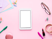 Pink pastel flat lay with gadget tablet smartphone stationery glasses woman lipstick, bracelets. White screen