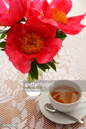 Pink flowers in vase and tea cup on table. : Stock Photo