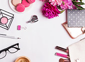 Modern trendy flat lay photo: pink flowers, macarons, feminine accessories