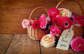 pink flowers in the basket next to the card with phrase: I LOVE YOU, on wooden table