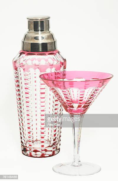 Pink glass mixer with matching martini glass against white background