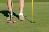 Pink colored golf ball by the flag and hole on putting green senior man tries to sink the ball with putter
